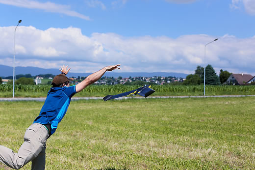 Man throwing a drone in a field